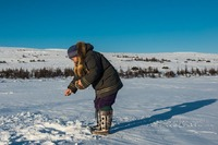 Ice fishing with Inuit woman around Kangiqsualujjuaq, Canada