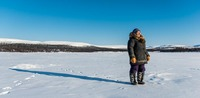 Inuit woman looking for fishing spot around Kangiqsualujjuaq, Canada