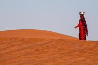 A woman carrying water for her animals through the Empty Quarter Desert in Oman.