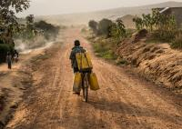 A refugee is transporting water in Uganda.