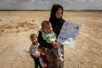 Syrian refugee mother with her two children in the desert like area in Jordan and their UNHCR registration paper.