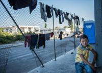 Afghani refugee boy watching the families drying clothes on the fence in the old airport in Athens, Greece.