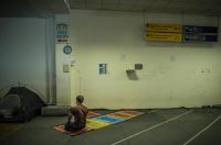 In greece, an Irani refugee pray  in the old Athens airport in the old departure terminal.