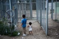Afghani refugee children in the make-shift camp are looking at the fence of the closed border crossing between the Hungarian and Serbian border in  Horgos Serbia.