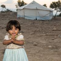 "Syrian refugee girl is standing by her ""home"" in an informal settlement in Jordan Valley, Jordan."