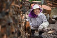 Woman working with logs of wood in northern Hokkaido, Japan